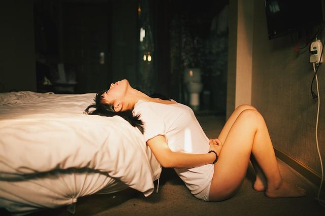 Žena v bielom tričku je opretá v sexy póze o posteľ.jpg