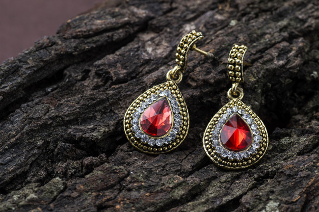 pair-earrings-wooden-space_136354-1783
